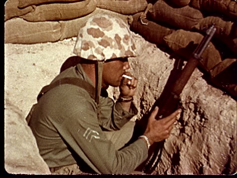 1950s ms soldier crouching in trench holding rifle and smoking cigarette at camp desert rock at nevada test site / nye county nevada usa - campo militare video stock e b–roll