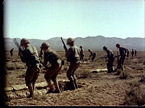 1950s ws soldiers jumping into trenches in desert at camp desert rock at nevada test site / nye county nevada usa - campo militare video stock e b–roll
