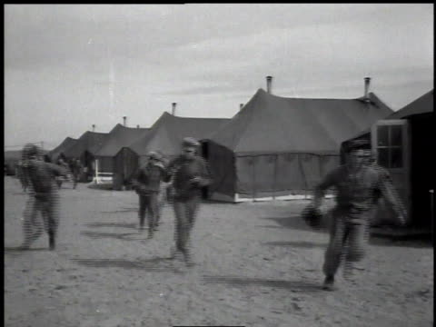 1950s soldiers rushing out of tents, putting on helmets / hanford, washington, united states - allarme di prova video stock e b–roll