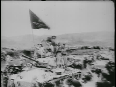B/W 1950s PAN soldiers waving holding flag riding tank in military parade / North Vietnam
