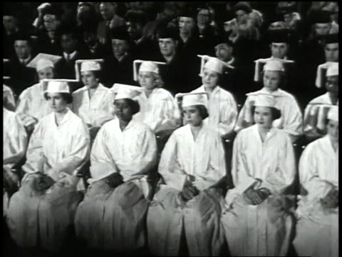 vidéos et rushes de 1950s pan students sitting in graduation gowns at a commencement ceremony/ united states - film documentaire image animée