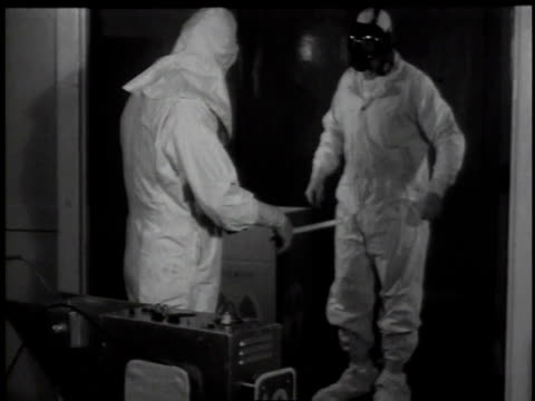1950s ms technician checking another worker for radiation / hanford, washington, united states - contatore geiger video stock e b–roll