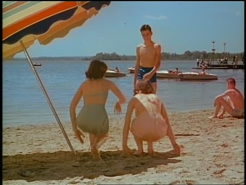 1950s teen boy greeting 2 girls in bikinis on beach / they run into water