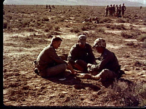 vídeos de stock e filmes b-roll de 1950s three army soldiers sitting cross-legged playing cards at camp desert rock at nevada test site / nye county, nevada, usa - cross legged