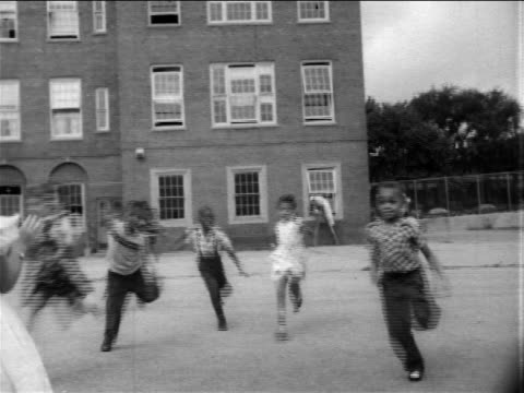 B/W 1950s tilt down Black schoolchildren running + tripping on playground toward camera / newsreel