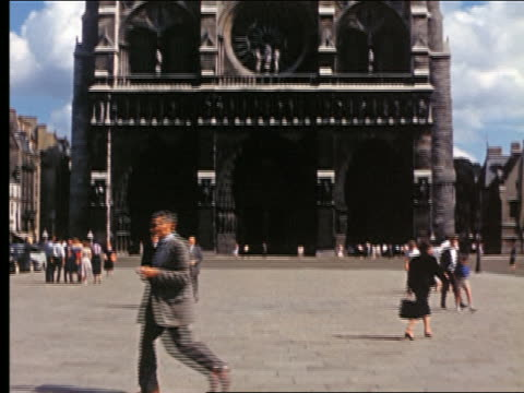 1950s tilt up facade of cathedrale notre dame / people walking in front in foreground / paris, france - notre dame de paris stock videos & royalty-free footage