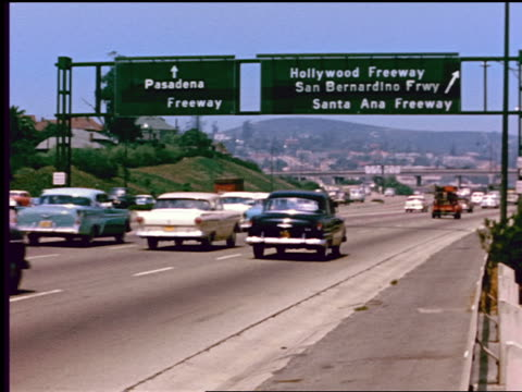 1950s traffic on freeway in Los Angeles / signs for Pasadena, Hollywood + San Bernardino Freeways