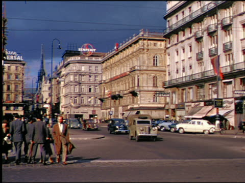 1950s traffic + people crossing street with buildings in background / vienna, austria - vienna austria stock videos & royalty-free footage