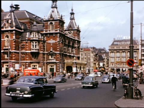 vídeos de stock, filmes e b-roll de 1950s traffic, people walking + riding bicycles on dutch city street with large ornate building in background - países baixos