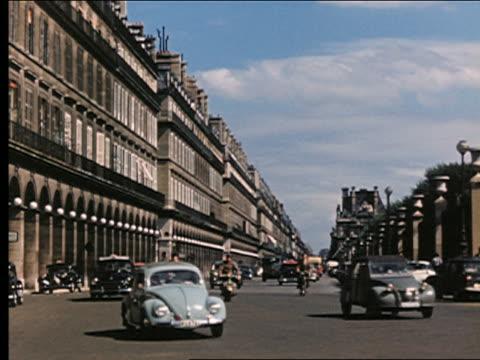 1950s traffic + scooters turning corner on rue rivoli next to louvre / paris, france - paris france video stock e b–roll