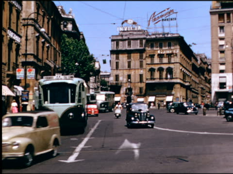 1950s traffic with cable buses + scooter at intersection / Rome, Italy