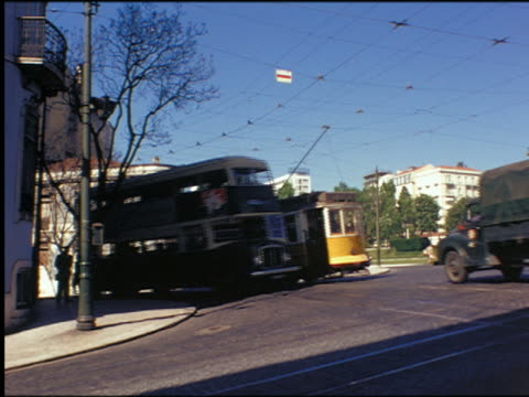 1950s trolley, truck + double decker bus passing on city street / portugal - trolley bus stock videos & royalty-free footage