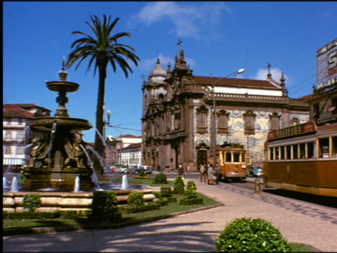 1950s trolleys passing small city park with fountain + palm tree / building in background / Portugal