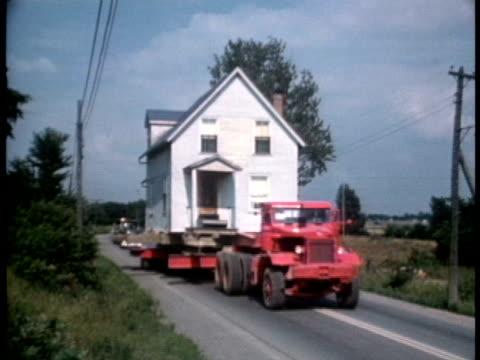 vídeos de stock e filmes b-roll de 1950s ws pan ms truck transporting house on highway - camião