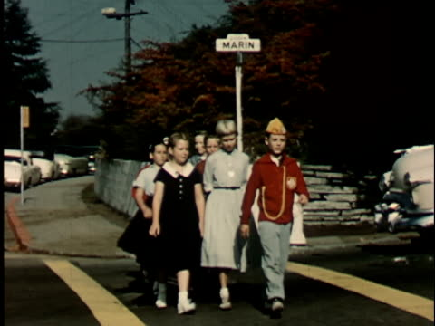 1950s MS, Two boys (12-13) in junior police uniforms assisting group of children crossing street, Berkeley, California, USA