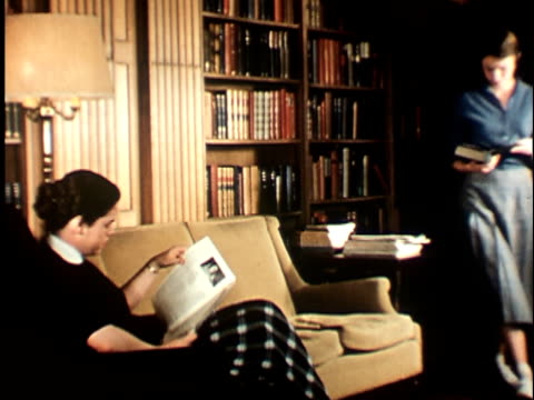 vídeos de stock, filmes e b-roll de 1950s ms, two female students reading books in library at berkeley university, 1950's, california, usa - esetante de livro
