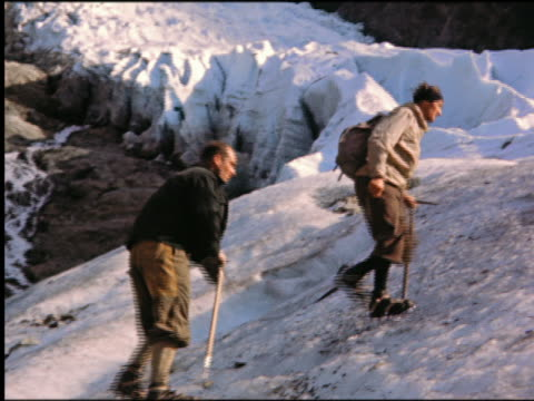 stockvideo's en b-roll-footage met 1950s two men wearing crampons + carrying pick-axes walking up icy slope of mountain / (mont blanc?) / italian alps / italy - pikken