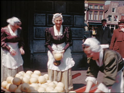 1950s two women in traditional dress tossing balls of cheese to third woman / netherlands - traditional clothing stock videos & royalty-free footage