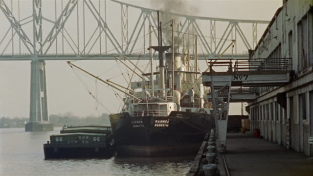 1950s WS Wharf and ferry, bridge in background, New Orleans, Louisiana, USA