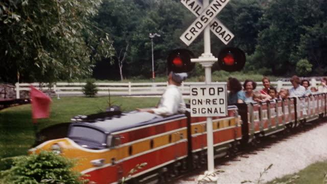 vidéos et rushes de 1950s wide shot families on train ride passing traffic signal / zoom in young boy waving at cam - monter sur un moyen de transport