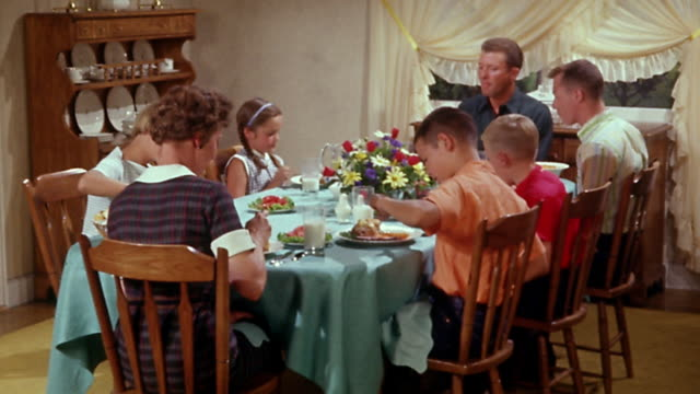 vídeos de stock e filmes b-roll de 1950s wide shot family eating meal at dinner table - 1950