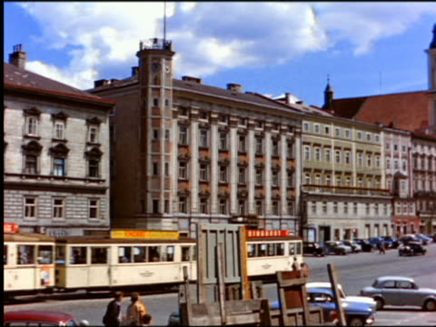 vidéos et rushes de 1950s wide shot pan from trolley + traffic on street lined by buildings to column of the plague / vienna - autriche