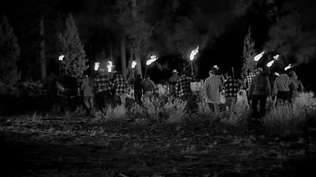 1950s wide shot group of men in search party with torches walking into forest at night