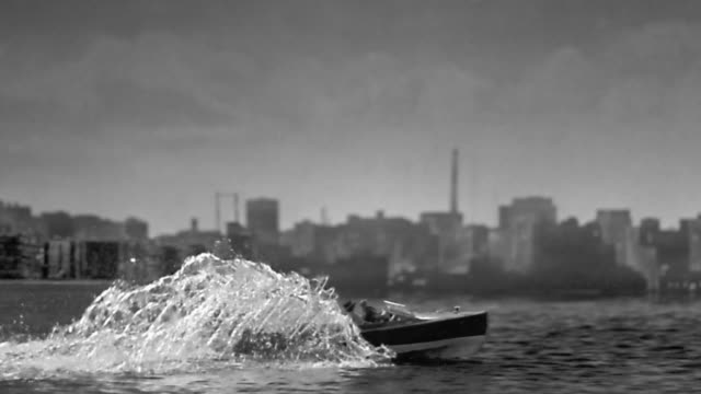 1950s wide shot pan small boat hitting barge and exploding / staged - lastkahn stock-videos und b-roll-filmmaterial