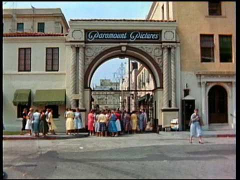1950s wide shot Paramount Pictures gate w/line of women outside and cars passing / Hollywood, CA