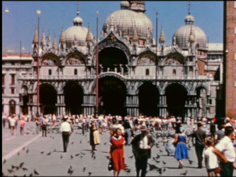 1950s wide shot pigeons + crowds of people in front of Basilica San Marco / St Mark's Square (Piazza di San Marco) / Venice, Italy