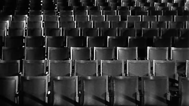 1950s wide shot seats in empty theater / blur and dissolve effects - biosalong bildbanksvideor och videomaterial från bakom kulisserna