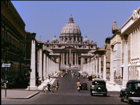 1950s wide shot St Peter's Basilica (Basilica di San Pietro) with column-lined street with traffic in foreground / Vatican City / Rome, Italy
