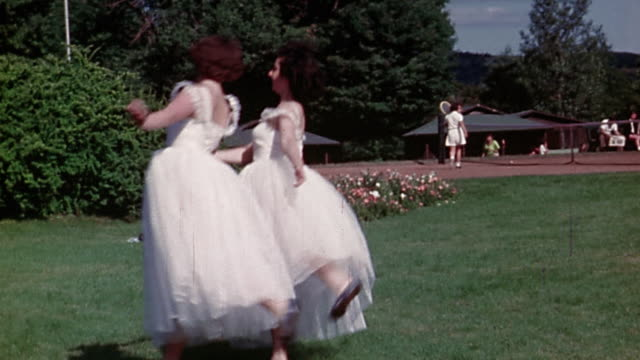 vidéos et rushes de 1950s wide shot tracking shot 2 young women wearing long white dresses dancing in park - style rétro
