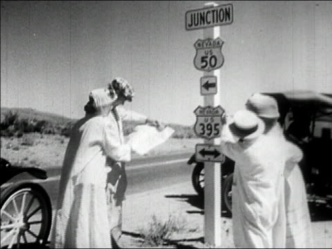 1950s Wide shot two couples looking at map near road signs with old car in background/ AUDIO