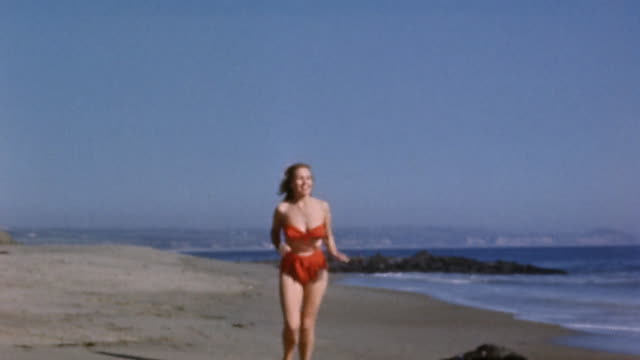 1950s wide shot woman in red bikini swimsuit running on beach, looking into distance - bikini stock-videos und b-roll-filmmaterial