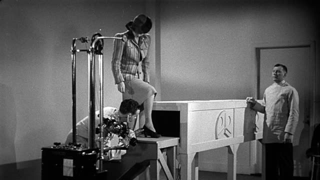 b/w 1950s wide shot woman standing on x-ray machine with doctor positioning her foot / other doctor watching - x ray equipment stock videos & royalty-free footage