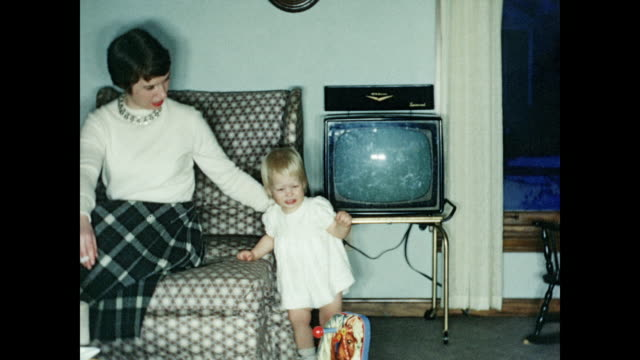 1950s Woman and baby in living room, baby crawling on floor