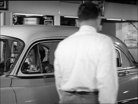 b/w 1950s woman driving car into service station + talking to attendant - filling station attendant stock videos & royalty-free footage