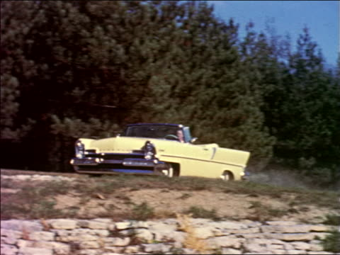 1950s PAN woman driving yellow convertible Lincoln on dirt road / industrial