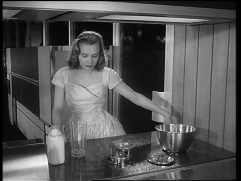 b/w 1950s woman pushes button + blender pops up from counter, pours beverage in + turns it on - 10 seconds or greater stock videos & royalty-free footage