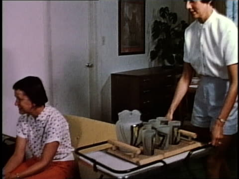 1950s ts woman rolling a cart with drinks to people in a living room / levittown, pennsylvania, united states - levittown pennsylvania stock videos and b-roll footage
