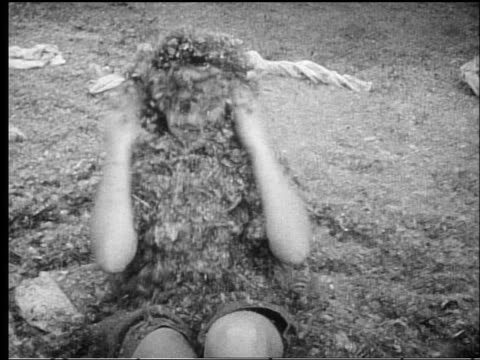 b/w 1950s ms woman sitting up covered with feathers after pillow fight outdoors - pillow fight stock videos & royalty-free footage