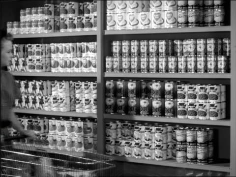 b/w 1950s woman taking can off supermarket shelf - hausfrau stock-videos und b-roll-filmmaterial