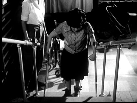 """stockvideo's en b-roll-footage met """"1950s ms woman with braces on legs climbing up stairs using crutches/ st. louis, missouri"""" - 1959"""