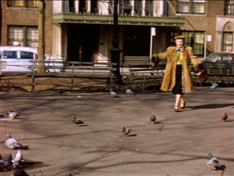 1950s woman with bright red hair + leopard skin coat running through park + scaring pigeons / NYC