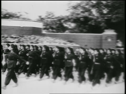 b/w 1950s pan women in black uniforms marching in parade / north vietnam / newsreel - north vietnam stock videos and b-roll footage
