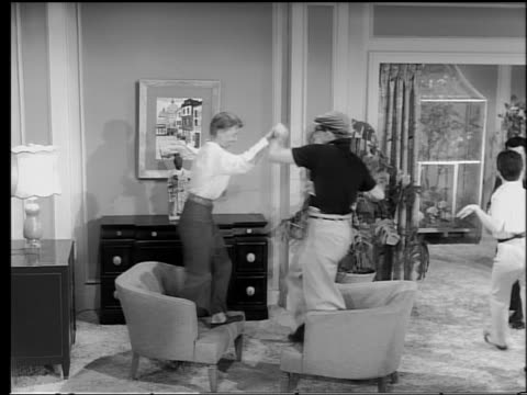 B/W 1950s young couple dancing on chairs in living room / other couple dancing in background