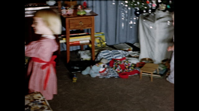 1950s young girl playing with rocking horse on christmas day home movie - 1950年点の映像素材/bロール