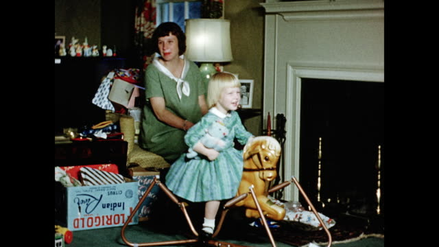 vidéos et rushes de 1950s young girl playing with rocking horse on christmas day home movie - film d'amateur
