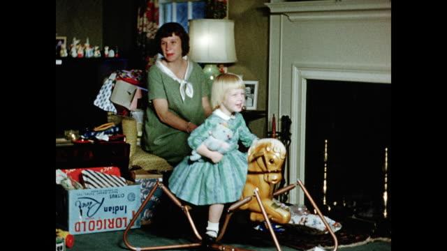 vídeos de stock e filmes b-roll de 1950s young girl playing with rocking horse on christmas day home movie - família com quatro filhos